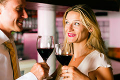 Man and woman flirting in hotel bar. Man and woman in a hotel bar in the evening having glasses of red wine and a little flirt stock photos