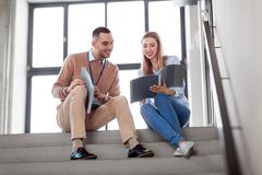 Man and woman with folders at office stairs Royalty Free Stock Image