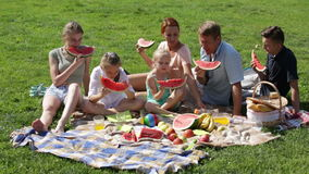 Man and woman with four kids having watermelon on picnic stock footage