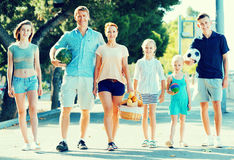 Man and woman with four kids smiling and taking walk. Smiling happy men and women with four cheerful satisfied kids smiling and taking walk in town Stock Photos
