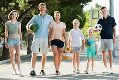 Man and woman with four kids smiling and taking walk. Smiling happy men and women with four cheerful satisfied kids smiling and taking walk in town Stock Image