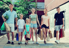 Man and woman with four kids walking and holding shopping bags Royalty Free Stock Photos