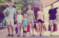 Man and woman with four kids walking and holding shopping bags Royalty Free Stock Image