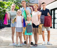 Man and woman with four kids walking and holding shopping bags Royalty Free Stock Photo