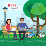 Man and woman freelancers works in park with computer on bench under tree. Royalty Free Stock Photos