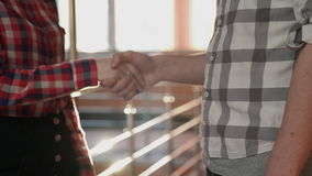 The man and woman friendly shake hands in the hallway with sunlight. The guy in plaid gray shirt stretches out his hand for what to take a brush woman in a red stock footage
