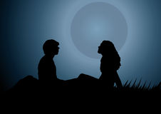 Man and a woman in front of the full moon. Silhouette of a man and a woman lying on the grass in front of the full moon Stock Photos