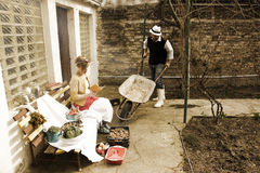 Man and Woman in Garden-gardening concept. Woman is Sitting on Garden Bench and Reading Book to Man with Wheelbarrow Royalty Free Stock Photography