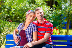 Man and woman in garden sitting on bench Stock Photography