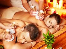 Man and woman getting herbal ball massage in spa. Man and woman getting herbal ball massage in bamboo spa stock photos