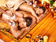 Man and woman getting herbal ball massage in spa. Man and woman getting herbal ball massage in bamboo spa stock image