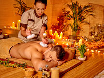 Man and woman getting herbal ball massage in spa Stock Photography