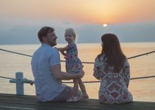 Man woman and girl on the beach - family. Mom, Dad and daughter are watching the dawn on the pier. A girl looks at the camera, parents look at her Stock Photo