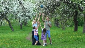 Man woman girl and boy catching ball in nature. Slow motion shot. Man woman girl and boy catching ball in nature. Active family play with ball in spring garden stock video footage