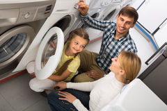 Man and woman with girl buying washing machine Royalty Free Stock Image
