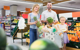 Man and woman with girl choosing fruits Stock Images