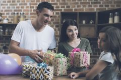 A man and a woman give gifts to a sad girl who turns away from them. Smiling mother and father congratulate the girl on the day of the birth of a women and give Stock Photography