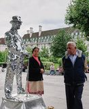 Indian couple check out motionless, silver mirrored street performer in London, England stock photo