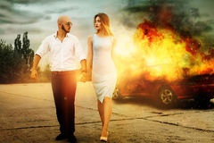 Man and a woman go away from burning car Stock Photo