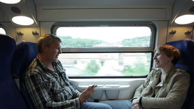 Man and woman go by  train sitting  friend opposite to  friend stock footage
