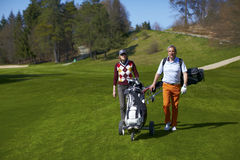 Man and woman golfers walking on a golf course. Man and woman golfers walking on a green golf course with golf bag and a trolley Stock Photography