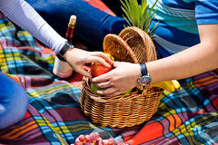 The man and the woman grabbed for an apple at a picnic Stock Photo