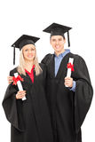 Man and woman in graduation gowns holding diplomas Royalty Free Stock Photos