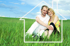 Man and woman in green field. Man and woman in house on green field  under blue sky Stock Photo