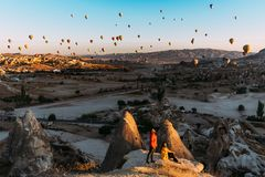 Man and woman greet the dawn among balloons. Couple in love among balloons. Travelers in the mountains of Cappadocia, Turkey. stock photos