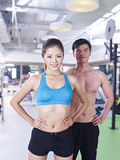 Man and woman in gym. Young women posing with her partner in fitness center Royalty Free Stock Image