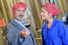 Man and woman in hairnets holding glass wine Royalty Free Stock Photos