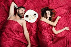 Man and woman with half covered bodies lie in bedroom. Man and women with half covered bodies lie in bedroom. Guy with beard and calm face has romantic breakfast royalty free stock photos