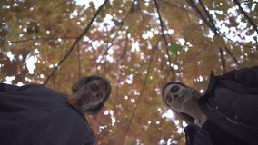 Man and woman in Halloween costumes looking down on the victim with serious scary faces in autumn park. The man showing stock video footage