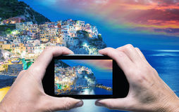 Man and woman hand capturing Cinque Terre sunset with smartphone Stock Photo