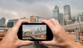 Man and woman hand capturing Hong Kong skyline with smartphone Stock Image