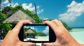 Man and woman hand capturing Maldivian Island colors with smartp Stock Image