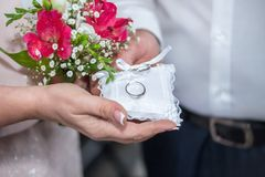 Man and woman hands with a bouquet of flowers holding a small pi. Llow with silver wedding rings.Concept : renewing marriage vows after 25 years which is Stock Photo