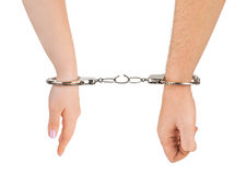 Man and woman hands and breaking handcuffs. Isolated on white background Stock Photos