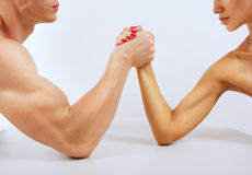 A man and woman with hands clasped arm wrestling, isolated. A men and women with hands clasped arm wrestling, isolated on white Royalty Free Stock Photo