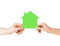 Man and woman hands with green paper house Stock Image