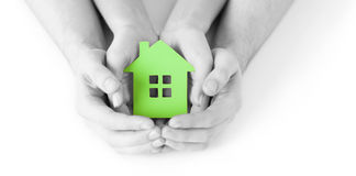 Man and woman hands with green paper house stock photos