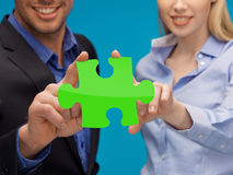 Man and woman hands with green puzzle Royalty Free Stock Photo
