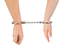 Man and woman hands and handcuffs. Isolated on white background Royalty Free Stock Photography
