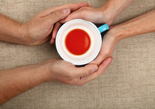 Man and woman hands hold empty black tea cup Stock Photos