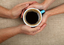 Man and woman hands hold full black coffee cup Stock Photos