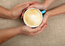 Man and woman hands hold full latte coffee cup Stock Images
