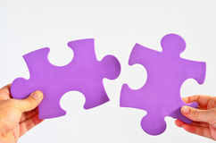Man and woman hands holds two different puzzle pieces separated Royalty Free Stock Image