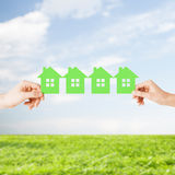 Man and woman hands with many green paper houses Stock Images