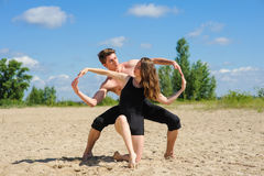 Man and woman hands showing infinity symbol. Contemporary dance. Man and women in passionate dance pose on beach. Young couple dancing modern dance outdoors. Man stock photography