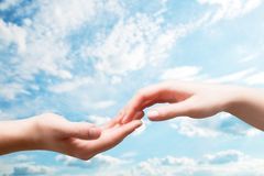 Man and woman hands touch in gentle, soft way on blue sunny sky royalty free stock photography